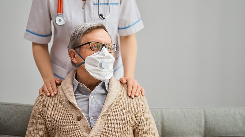 Man with a protective mask and healthcare professional